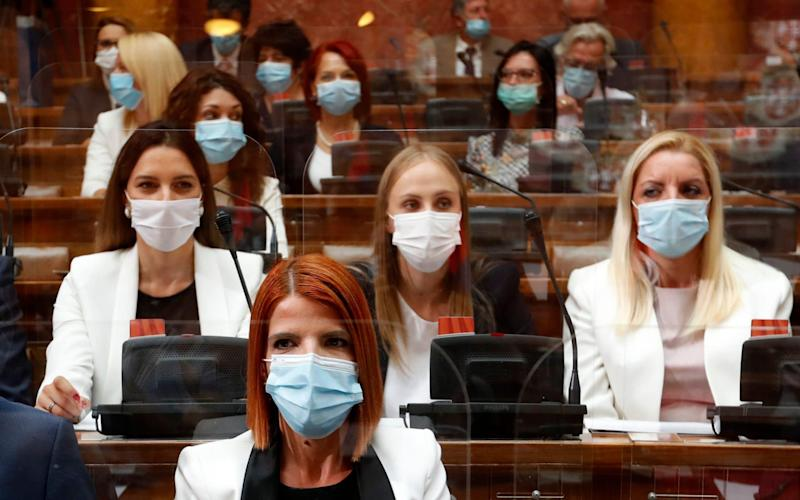 Serbian lawmakers wearing face masks to prevent the spread of coronavirus, take part in the inaugural parliament session. - AP Photo/Darko Vojinovic