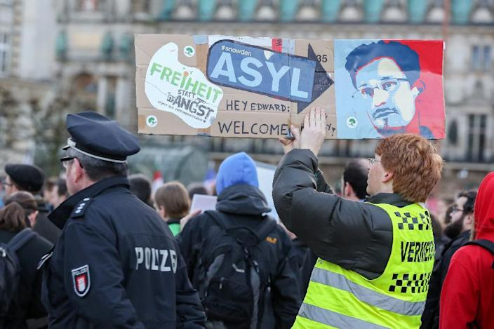 """Protestors hold up placards featuring a picture of former NSA contractor Edward Snowden with the world """"Asylum"""" during a march against the spying methods of the US in Hamburg, on December 28, 2013 (AFP Photo/Bodo Marks)"""