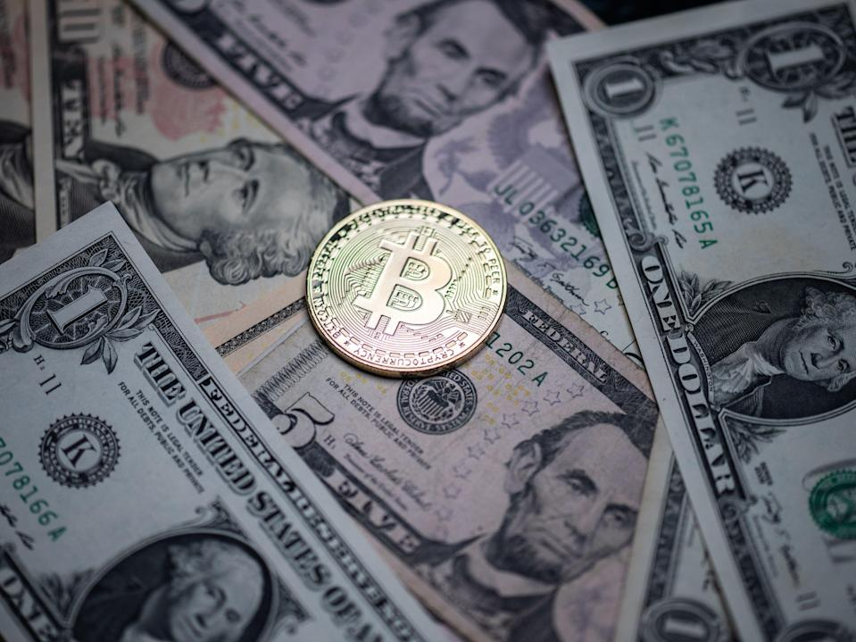 A physical imitation of the cryptocurrency is displayed on US bank notes (MARTIN BUREAU/AFP via Getty Images)