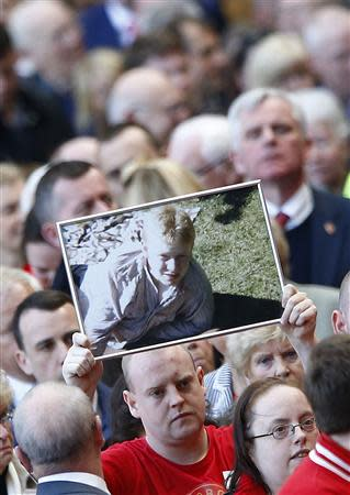 A man holds up a picture of a victim during a memorial service to mark the 25th anniversary of the Hillsborough disaster at Anfield in Liverpool, northern England April 15, 2014. REUTERS/Darren Staples