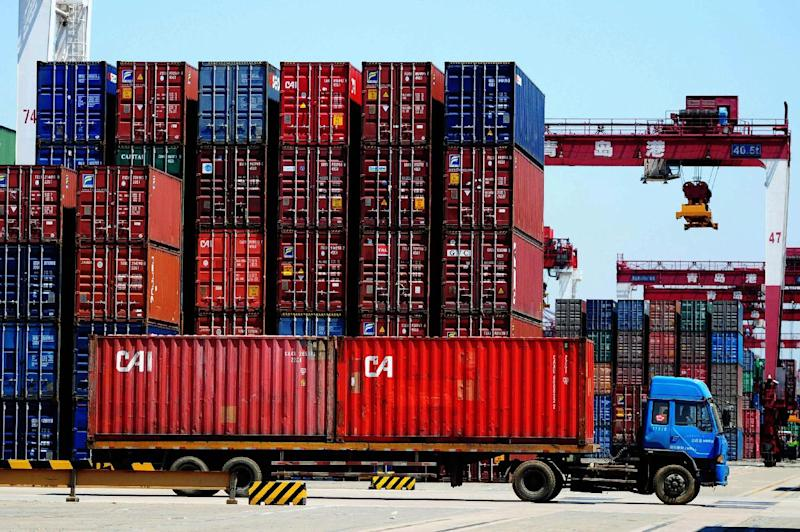 In this photo taken Saturday, May 3, 2014, a truck drives past containers at a port in Qingdao in east China's Shandong province. China's trade rebounded in April from the previous month's surprise contraction but imports were subdued in another sign of the country's economic slowdown. Customs data Thursday, May 8, 2014 showed exports rose 0.9 percent, recovering from March's 6.6 percent decline. Imports rose 0.8 percent, up from the previous month's 11.3 percent decline. (AP Photo) CHINA OUT