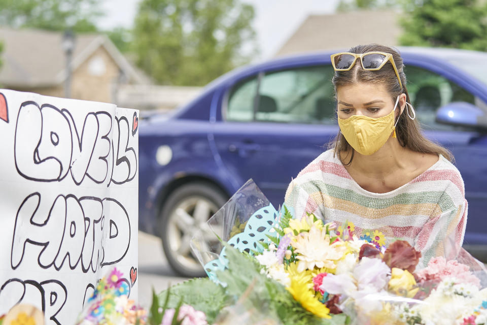 <p>A woman places flowers at the scene of a hate-motivated vehicle attack in London, Ont. on Tuesday, June 8, 2021, which left four members of a family dead and sent one to hospital on Sunday evening. THE CANADIAN PRESS/ Geoff Robins</p>