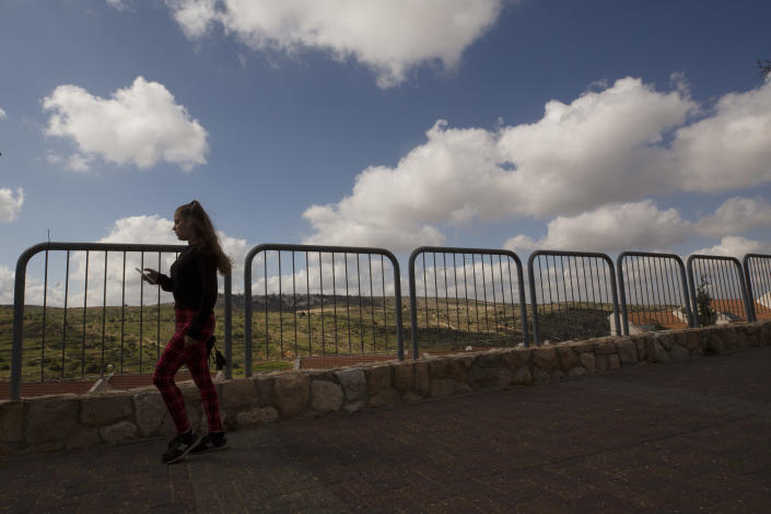 A woman takes a brisk walk in the West Bank Jewish settlement of Efrat, Friday, April 9, 2021. Israel went on an aggressive settlement spree during the Trump era, according to an AP investigation, pushing deeper into the occupied West Bank than ever before and putting the Biden administration into a bind as it seeks to revive Mideast peace efforts. (AP Photo/Maya Alleruzzo)