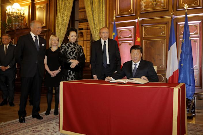 Chinese President Xi Jinping, right, signs a guest book as he is welcomed by Lyon's mayor Gerard Collomb, second right, and French foreign minister Laurent Fabius, left, before a dinner at the town hall in Lyon, central France, Tuesday, March 25, 2014. Xi Jinping arrived in France for a three-day state visit. (AP Photo/Laurent Cipriani, Pool)