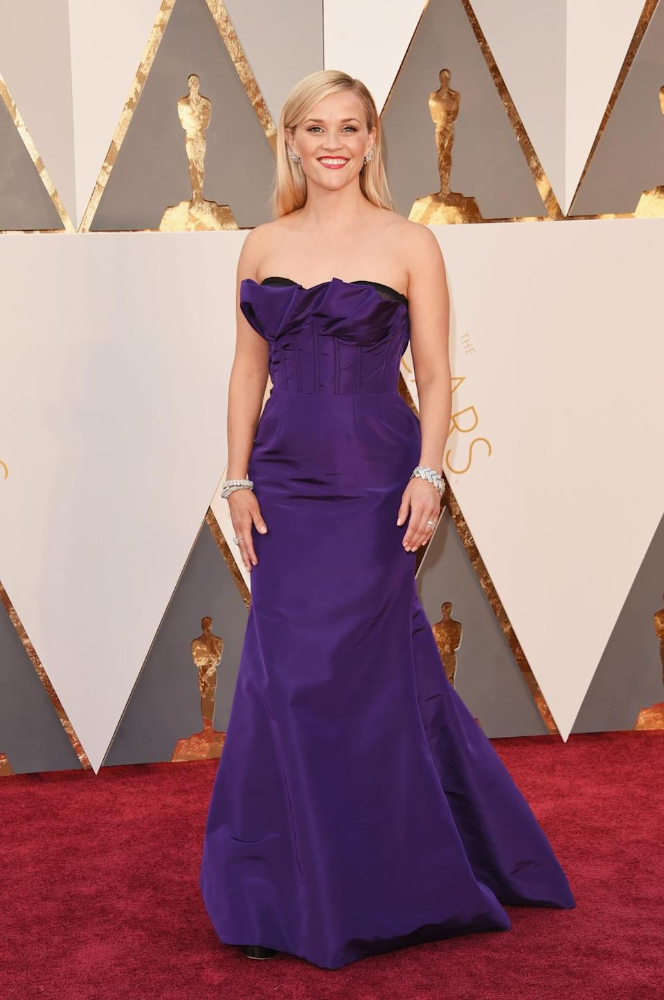 <p>Reese Witherspoon twinned with Tina Fey in a purple strapless gown from Oscar de la Renta. <i><i>(Photo: Getty Images)</i></i></p>