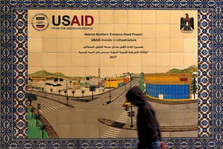 FILE PHOTO: Palestinian walks past a ceramic sign of a USAID project in Hebron in the Israeli-occupied West Bank