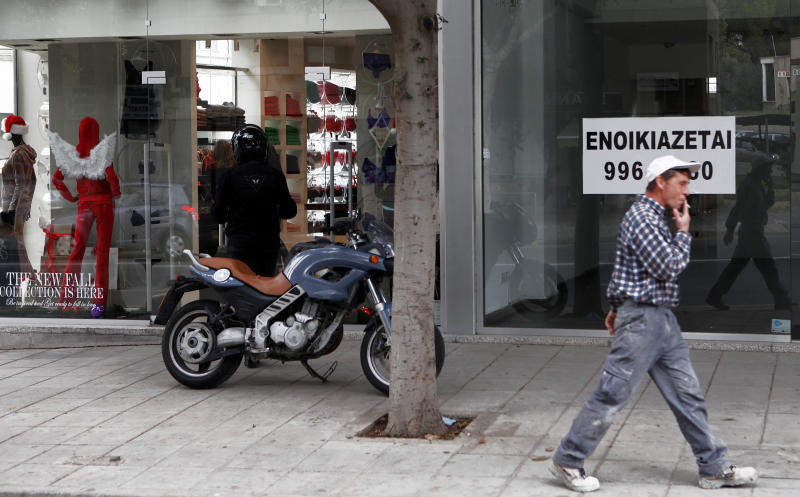 A man  smokes a cigarette as he passes in front of a sign advertising a retail location for rent as another man parks his motorcycle outside  a clothing shop at central Nicosia, Monday, Dec. 17, 2012. Cyprus' state coffers are depleted and government workers may go unpaid this month unless state-owned companies urgently lend the government some €250 million ($329 million) from their pension funds, the finance ministry's top civil servant warned Monday. (AP Photo / Petros Karadjias)