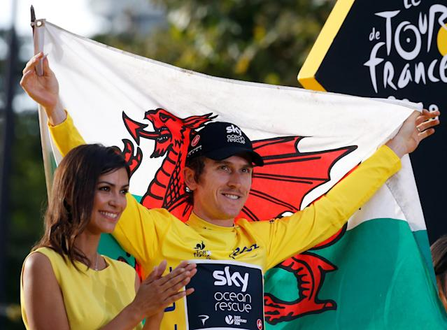 Team Sky rider Geraint Thomas of Britain celebrates his overall victory of the Tour de France on the podium with a Welsh flag on July 29, 2018. REUTERS/Stephane Mahe