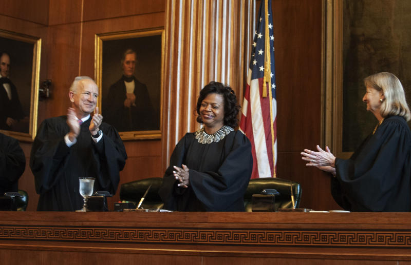 """FILE - In this March 7, 2019, file photo, Associate Justices Paul Newby, left, and Robin Hudson, right, applaud for new Chief Justice Cheri Beasley of the N.C. Supreme Court during Beasley's investiture ceremony in Raleigh, N.C. North Carolina's highest court heard arguments Monday, Aug. 26, on the repealed Racial Justice Act, which allowed condemned inmates to seek a life sentence by using statistics to show that race tainted their trials. During the hearing, Chief Justice Beasley said it seemed an attorney was addressing issues greater than what the cases involved and that he was """"possibly asking this court to address something greater."""" (Paul Woolverton/The Fayetteville Observer via AP, File)"""