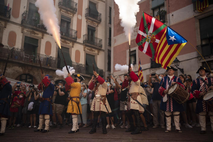 Men dressed in costume shoot their rifles during a performance to celebrate the Catalan National Day in Barcelona, Spain, Saturday, Sept. 11, 2021. Thousands of Catalan independence supporters have been called to take the streets of Barcelona for a march and speeches organised by the Assemblea Nacional de Catalunya, a pro-independence grassroots movement. ( AP Photo/Joan Mateu Parra)