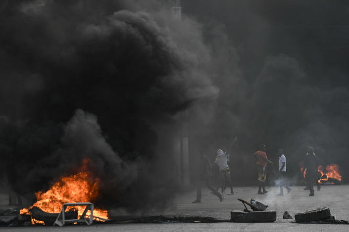 Protesters demanding justice for the assassinated President Jovenel Moise stand between burning barricades in Cap-Haitien, Haiti, Thursday, July 22, 2021. Demonstrations after a memorial service for Moise turned violent on Thursday afternoon with protesters shooting into the air, throwing rocks and overturning heavy concrete barricades next to the seashore as businesses closed and people took cover. (AP Photo/Matias Delacroix)