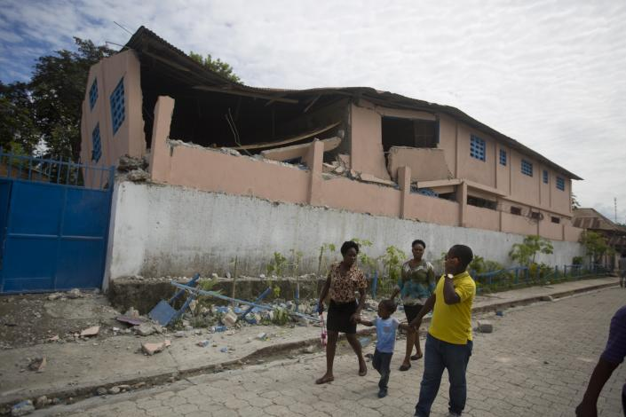 Residents walk past a school damaged by a magnitude 5.9 earthquake the night before, in Gros Morne, Haiti, Sunday, Oct. 7, 2018. Emergency teams worked to provide relief in Haiti on Sunday after the quake killed at least 11 people and left dozens injured. ( AP Photo/Dieu Nalio Chery)