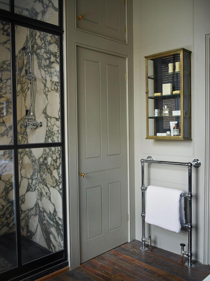 An antique brass cabinet is paired with a striking shower enclosure lined with Italian Seravezza Verde marble sourced in Italy and worked by Jamb.