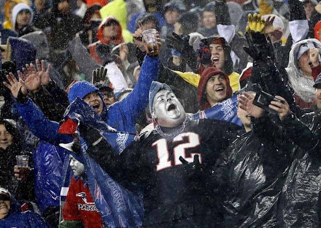 Rain-soaked New England Patriots fans cheer during the third quarter of an NFL football game between the Patriots and the Buffalo Bills, Sunday, Dec. 29, 2013, in Foxborough, Mass. The Patriots won 34-20, and will have a first-round bye in the AFC playoffs. (AP Photo/Elise Amendola)