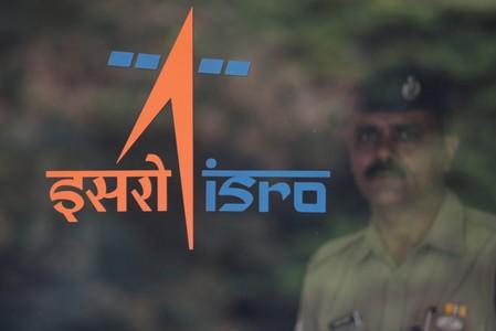 A security guard stands behind the logo of Indian Space Research Organisation (ISRO) at its headquarters in Bengaluru