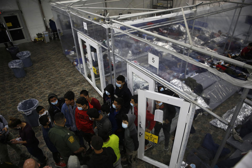 Minors talk to an agent outside a pod at the Department of Homeland Security holding facility run by the Customs and Border Patrol (CBP) on March 30, 2021 in Donna, Texas. The children are housed by the hundreds in eight pods that are about 3,200 square feet in size. Many of the pods had more than 500 children in them. (Dario Lopez-Mills - Pool/Getty Images)