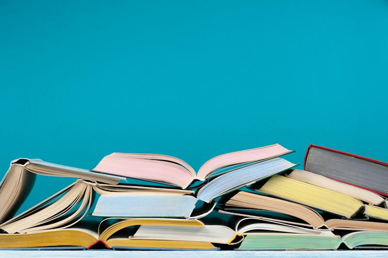 Hardback colorful books on blue background. Back to school. Copy space for text. Education business concept