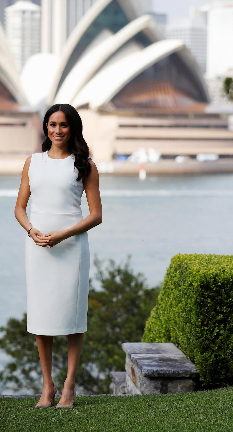 """<p>While it looked like a rather unassuming ivory design, the frock by Australian designer Karen Gee is actually called the """"Blessed Dress"""" – which is a feeling we're sure rings true for the excited parents to be. Meghan paired the look with nude stiletto heels and wore her hair in perfect, duchess waves. Photo: AAP </p>"""