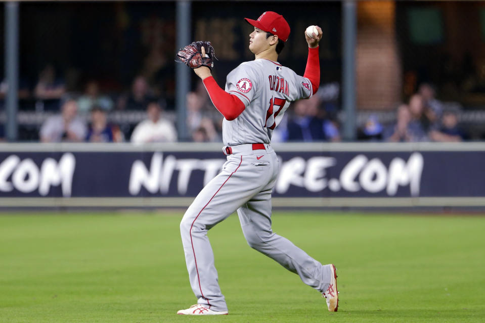 After switching to right field after pitching seven innings, Los Angeles Angels' Shohei Ohtani (17) fields the single by Houston Astros' Aledmys Diaz during the eighth inning of a baseball game Tuesday, May 11, 2021, in Houston. (AP Photo/Michael Wyke)