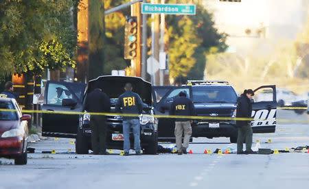FBI and police investigator are seen around a vehicle in which two suspects were shot following a mass shooting in San Bernardino, California December 3, 2015. REUTERS/Mike Blake
