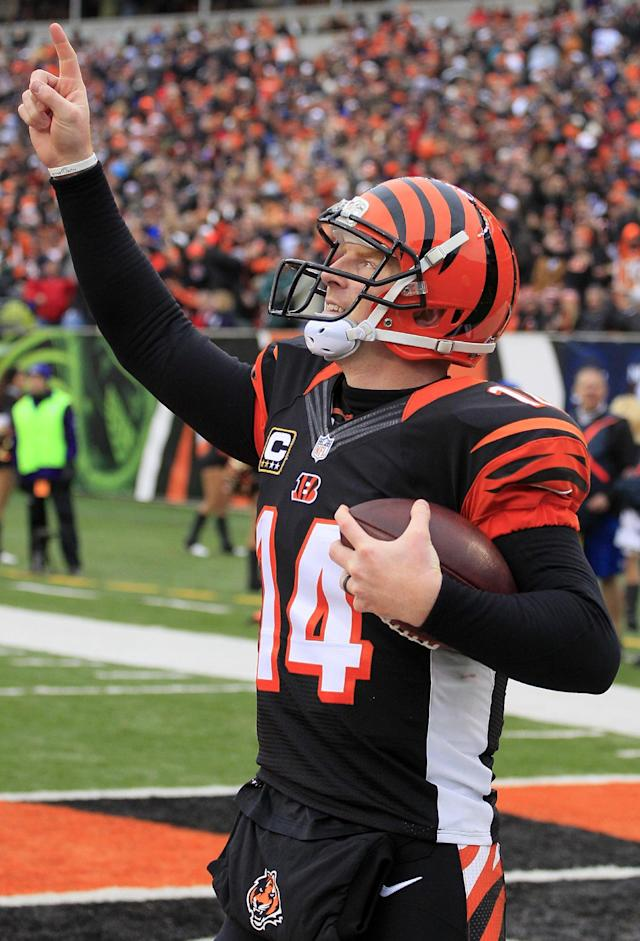 FILE - In this Dec. 29, 2013 file photo, Cincinnati Bengals quarterback Andy Dalton celebrates after scoring on a 1-yard touchdown run in the second half of an NFL football game against the Baltimore Ravens, in Cincinnati. Dalton is comparing himself with some of the NFL's top quarterbacks while negotiating a contract extension with the Cincinnati Bengals. He knows the one stat that's holding him back: 0-3 in the postseason. (AP Photo/Tom Uhlman, File)