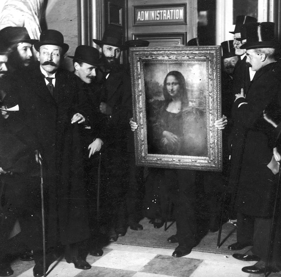 """Officials gather around Leonardo da Vinci's <em>Mona Lisa</em> upon its return to the <a href=""""https://www.cntraveler.com/activities/paris/louvre-museum?mbid=synd_yahoo_rss"""" rel=""""nofollow noopener"""" target=""""_blank"""" data-ylk=""""slk:Musée du Louvre"""" class=""""link rapid-noclick-resp"""">Musée du Louvre</a> on January 4, 1914. The famous painting was stolen by Vincenzo Peruggia in 1911 and it took three years to recover."""