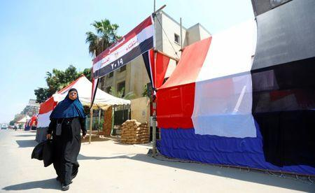 An Egyptian woman walks in front of a polling station covered from outside by Egyptian flags, during the preparations for the upcoming referendum on constitutional amendments in Cairo, Egypt April 18, 2019. REUTERS/Amr Abdallah Dalsh