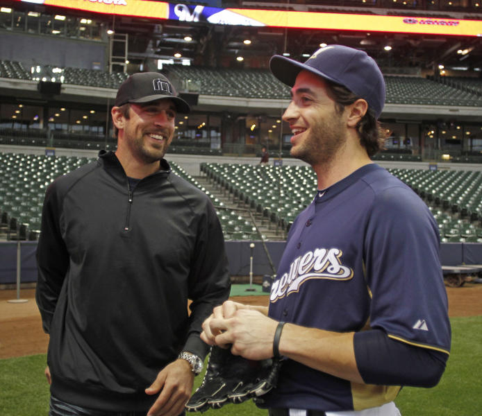 """FILE - In this June 9, 2011 file photo, Green Bay Packers NFL football quarterback Aaron Rodgers, left, and Milwaukee Brewers outfielder Ryan Braun speak during batting practice before a baseball game between the Brewers and the New York Mets,, in Milwaukee. Rodgers says he was """"shocked"""" when his friend Ryan Braun admitted he violated baseball's rules against using performance-enhancing substances. (AP Photo/Jeffrey Phelps, File)"""