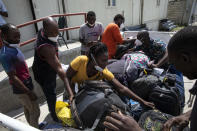 Haitian migrants deported from the US pick up their luggage at the Toussaint Louverture International Airport in Port-au-Prince, Haiti, Sunday, Sept. 19, 2021. Thousands of Haitian migrants have been arriving to Del Rio, Texas, to ask for asylum in the U.S., as authorities begin to deported them to back to Haiti which is in a worse shape than when they left. (AP Photo/Rodrigo Abd)