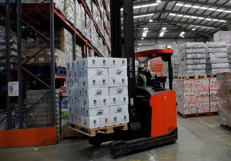 A worker moves coconut milk at Grace Foods UK distribution centre in Welwyn Garden City, Britain September 25, 2017. Picture taken September 25, 2017. To match Insight BRITAIN-EU/COMPANIES    REUTERS/Darren Staples