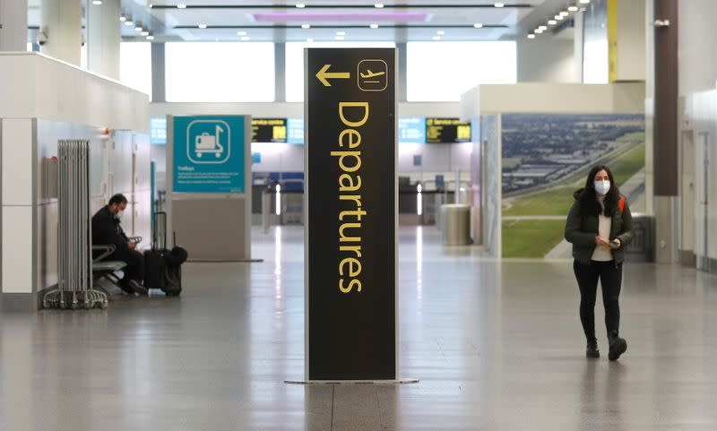 Passengers are seen in an almost empty check-in area at Gatwick Airport, amid the coronavirus disease (COVID-19) outbreak, in Crawley