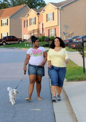 In this July 11, 2011 photo, Stormy Bradley, right, and her daughter Maya, 14, walk their dog Bubbles in their neighborhood in Atlanta. Maya, who is 5'4