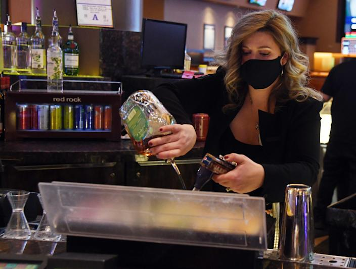 Maria Mahula wears a mask as she makes a drink June 4 at the Red Rock Resort in Las Vegas.