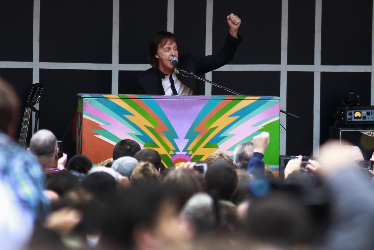 Singer Paul McCartney gestures as he plays a surprise mini-concert in New York's Times Square, October 10, 2013. REUTERS/Shannon Stapleton (UNITED STATES - Tags: ENTERTAINMENT)