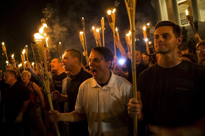 A white woman (far left) protests with a torch at the University of Virginia with neo-Nazis. (Anadolu Agency via Getty Images)