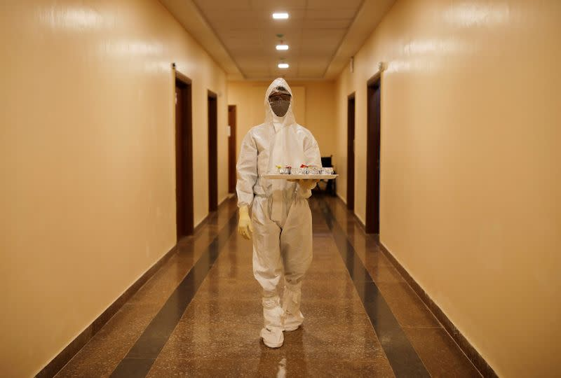 FILE PHOTO: A medical worker carries a tray with tea for the patients suffering from the coronavirus disease (COVID-19), at a hospital in Noida