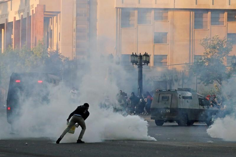 A demonstrator covers a tear gas canister in a bucket during a protest against Chile's state economic model in Santiago