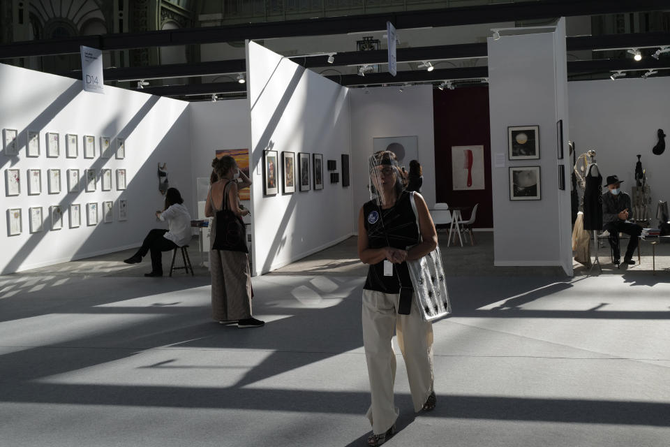A visitor, wearing a protective face mask as a precaution against the coronavirus, looks on during the opening day of Art Paris at the Grand Palais in Paris, Wednesday Sept. 9, 2020. Fears and restrictions over the coronavirus have caused the cancellation of all of 2020's premiere global art fairs, such as Art Basel, Frieze London, and Art Basel in Miami Beach, stymieing the main commercial artery of the multi-million-dollar industry.But organizers of Art Paris, France's second biggest contemporary art fair, have thrown caution to the wind, and are opening their doors to thousands of visitors from Thursday in the Grand Palais for a four-day show. (AP Photo/Francois Mori)