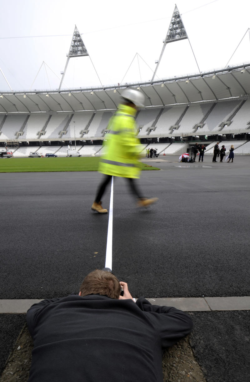 A photographer takes a picture of a construction worker crossing the finish line,at the London 2012 Olympic stadium,  London, Tuesday, March 29, 2011. The last piece of turf was laid Tuesday at the Olympic Stadium, symbolizing the completion of building work on the 80,000-seat flagship venue for the 2012 London Games. Former Olympic sprinter Frank Fredericks used a shovel to lay down the symbolic last piece of grass on the infield, 16 months before next year's games. (AP Photo/Tom Hevezi)