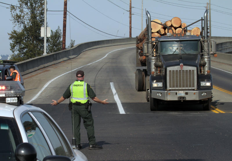 A Cowlitz County Sheriff officer directs traffic into the Port of Longview in Longview, Wash.,  Thursday, Sept. 8, 2011.  Hundreds of Longshore workers stormed the Port of Longview early Thursday, overpowered and held security guards, damaged railroad cars, and dumped grain that is the center of a labor dispute, said Longview Police Chief Jim Duscha.(AP Photo/Don Ryan)