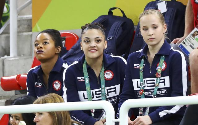 2016 Rio Olympics - Artistic Gymnastics - Final - Women's Individual All-Around Final - Rio Olympic Arena - Rio de Janeiro, Brazil - 11/08/2016. Gabrielle Douglas (USA) of USA (Gabby Douglas) (L), Laurie Hernandez (USA) of USA (C) and Madison Kocian (USA) of USA watch as their team mates (not pictured) Simone Biles (USA) of USA and Alexandra Raisman (USA) of USA (Aly Raisman) compete in the women's individual all-around final. REUTERS/Mike Blake FOR EDITORIAL USE ONLY. NOT FOR SALE FOR MARKETING OR ADVERTISING CAMPAIGNS.
