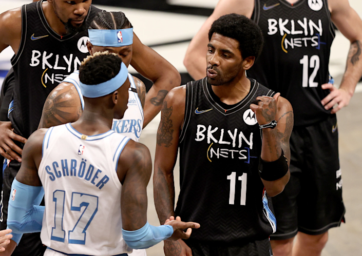 The Lakers' Dennis Schroder (17) and the Nets' Kyrie Irving (11) have words in the third quarter April 10, 2021.