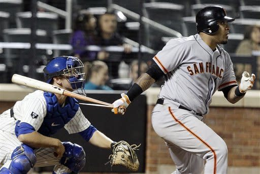San Francisco Giants' Hector Sanchez, right, hits a single to drive in a run during the tenth inning of a baseball game against the New York Mets, Friday, April 20, 2012, in New York. (AP Photo/Frank Franklin II)