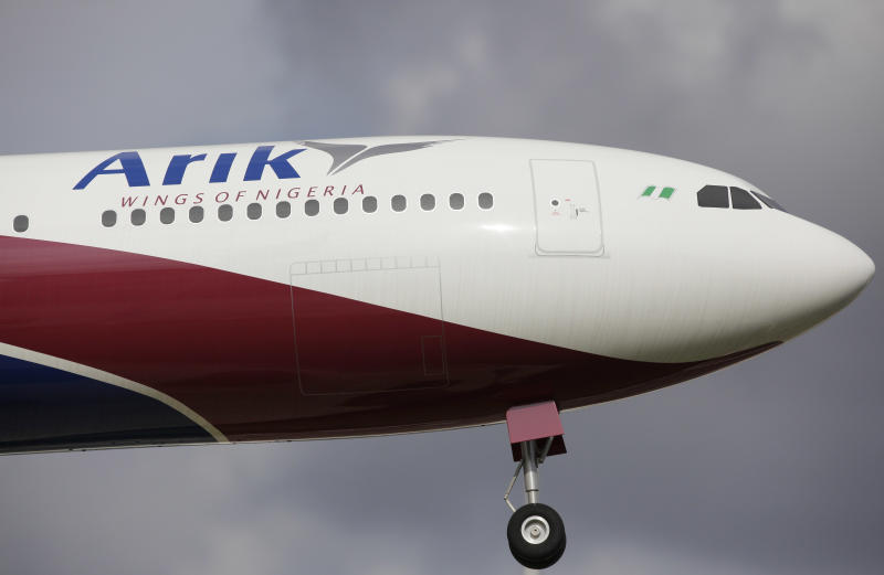 A model Arik Air plane is hanging outside the airline headquarters in Lagos, Nigeria. Thursday, Sept. 20, 2012. Nigeria's largest airline Arik Air Ltd. halted all its domestic flights indefinitely Thursday as its leaders alleged government corruption made it impossible for the carrier to fly, after officials raided and disrupted its flights without explanation.(AP Photo/Sunday Alamba)