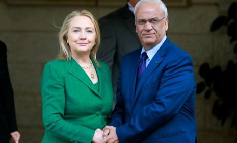 U.S. Secretary of State Hillary Clinton holds hands with senior Palestinian official Saeb Erekat after meeting with Palestinian President Mahmoud Abbas in the West Bank city of Ramallah on Nov. 21.