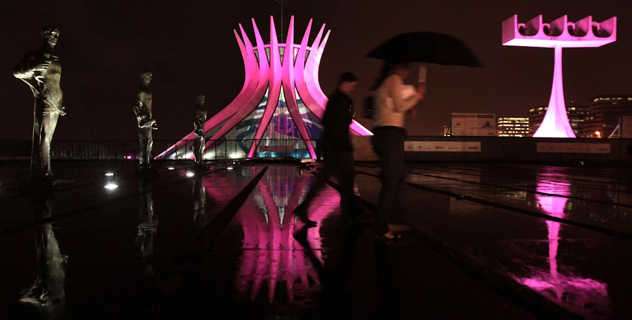 People walk in front of the Metropolitan Cathedral in Brasilia, Brazil, on Oct. 5, 2011. The cathedral is lit in pink to mark Breast Cancer Awareness Month.
