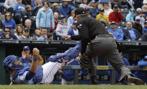 Kansas City Royals catcher Humberto Quintero, left, looks for the call after Toronto Blue Jays' J.P. Arencibia scored on single by Jose Bautista during the fifth inning of a baseball game on Sunday, April 22, 2012, in Kansas City, Mo. (AP Photo/Charlie Riedel)