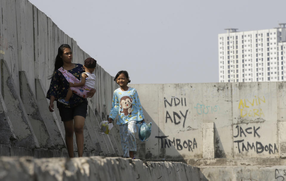 People walk near of a giant sea wall which is used as a barrier to prevent sea water from flowing into land and cause flooding in Jakarta, Indonesia, Saturday, July 27, 2019. Indonesia's President Joko Widodo said in an interview that he wants to see the speedy construction of the giant sea wall to save the low-lying capital of Jakarta from sinking under the sea, giving renewed backing to a long-delayed multi-billion-dollar mega project. (AP Photo/Achmad Ibrahim)