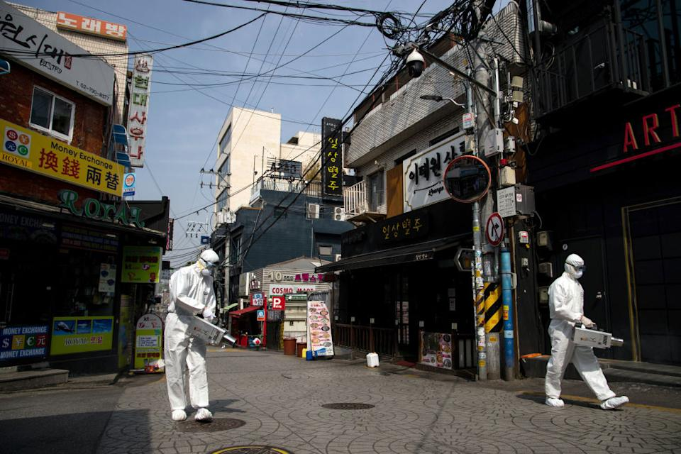 Photo shows workers in PPE spraying disinfectant in Seoul's Itaewon area to protect against the coronavirus.