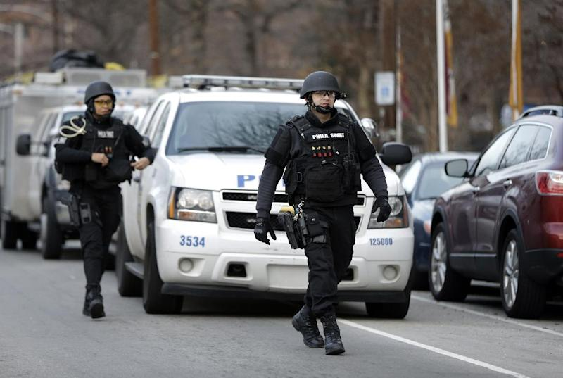 Police walk to the Delaware Valley Charter School Friday, Jan. 17, 2014, in Philadelphia. Police say two students have been shot at a Philadelphia high school. (AP Photo/Matt Rourke)